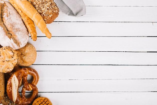 Een bovenaanzicht van brood assortiment op houten plank Gratis Foto
