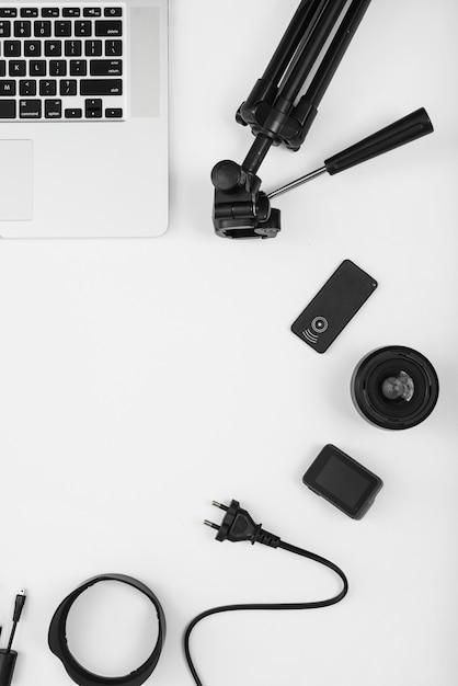 Een bovenaanzicht van camera-accessoire met laptop op witte achtergrond Gratis Foto