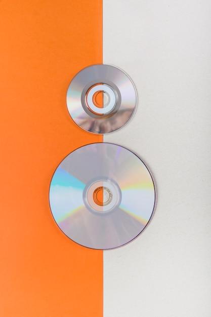 Een bovenaanzicht van cd's op een oranje en witte dubbele achtergrond Gratis Foto