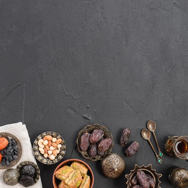 Een bovenaanzicht van datums; noten en baklava metalen platen op zwart beton getextureerde achtergrond met kopie ruimte Gratis Foto