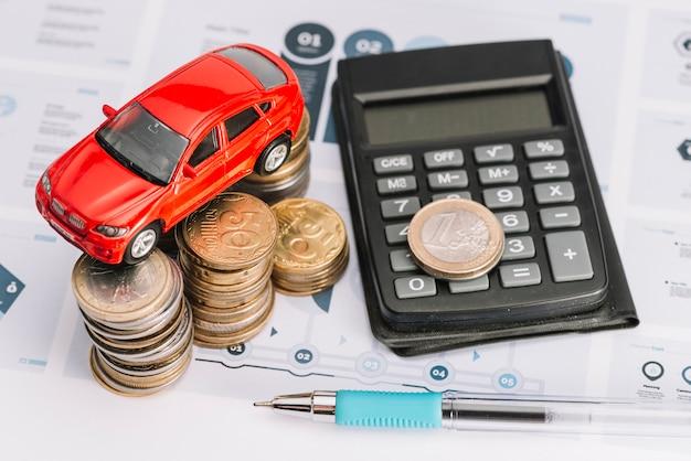 Een bovenaanzicht van de auto boven de stapel munten; rekenmachine en pen over de infographic sjabloon Premium Foto
