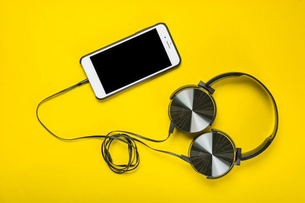 Een bovenaanzicht van de koptelefoon bevestigd met mobiele telefoon op gele achtergrond Gratis Foto