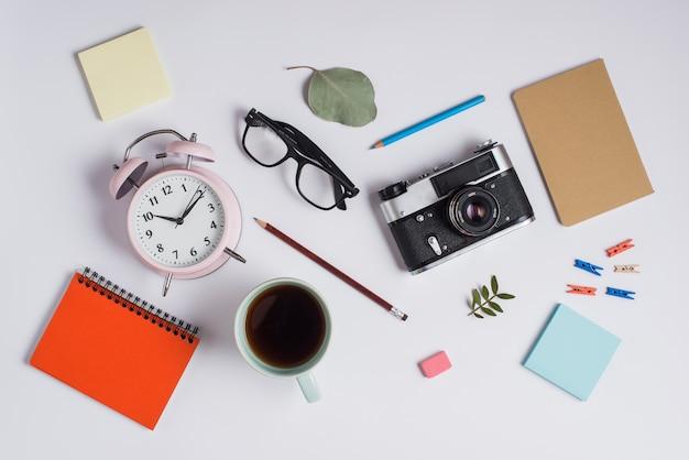 Een bovenaanzicht van de wekker; bril; camera; koffiekopje en kantoorbenodigdheden op witte achtergrond Gratis Foto
