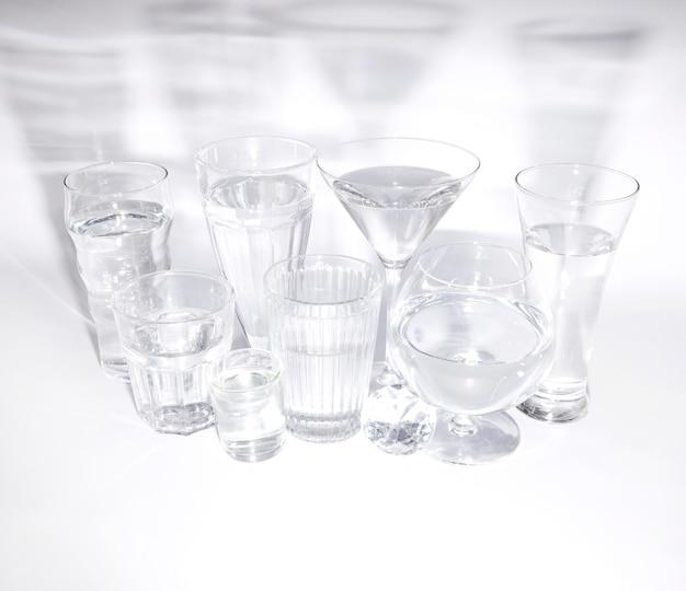 Een bovenaanzicht van diamant met glazen water met schaduw op witte achtergrond Gratis Foto