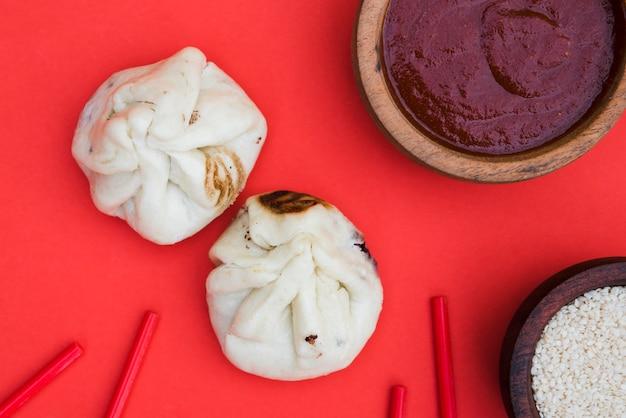 Een bovenaanzicht van dumplings; eetstokjes; sesamzaden en sauzen op rode achtergrond Gratis Foto