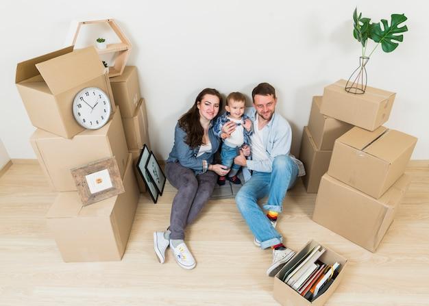 Een bovenaanzicht van een jong koppel met hun baby zitten tussen kartonnen dozen in hun nieuwe huis Gratis Foto