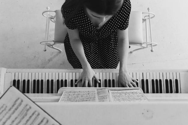 Een bovenaanzicht van een jonge vrouw die piano speelt Gratis Foto