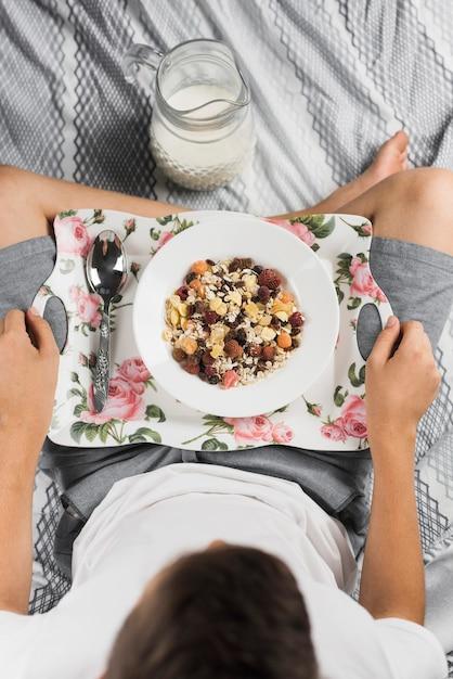 Een bovenaanzicht van een jongen zittend op bed met gekruiste been met gezonde haver maaltijd Gratis Foto