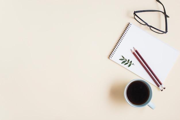 Een bovenaanzicht van een kopje thee; brillen en potlood op spiraalvormige blocnote tegen beige achtergrond Gratis Foto