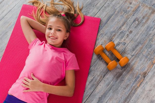 Een bovenaanzicht van een meisje liggend op oefening mat in de buurt van de halter Gratis Foto