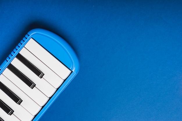 Een bovenaanzicht van elektronische synthesizer op blauwe achtergrond Gratis Foto