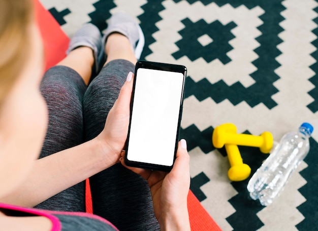 Een bovenaanzicht van fit jonge vrouw met mobiele telefoon weergeven leeg wit scherm Gratis Foto