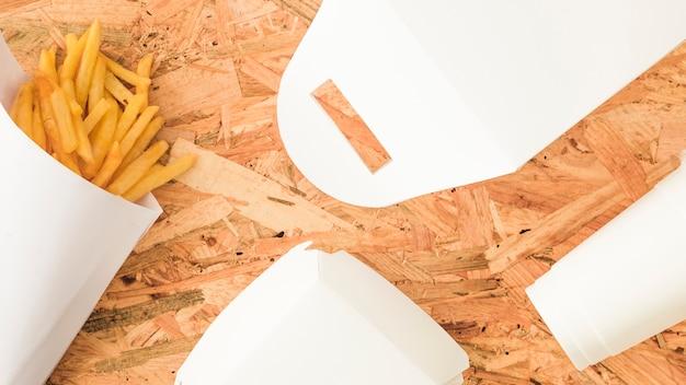 Een bovenaanzicht van franse frietjes en witte pakket op houten achtergrond Gratis Foto