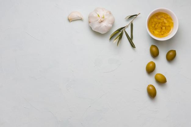 Een bovenaanzicht van gegoten olijfolie en knoflook in kom op concrete achtergrond Gratis Foto