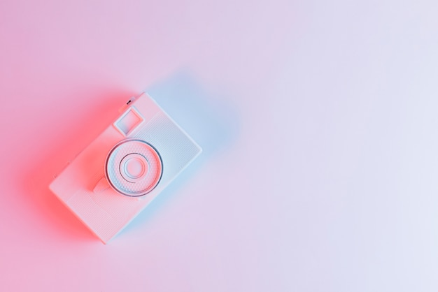 Een bovenaanzicht van geschilderde camera tegen roze achtergrond Gratis Foto