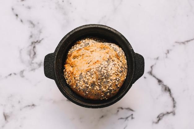 Een bovenaanzicht van gezond brood met zaden in de container op marmeren blad Gratis Foto