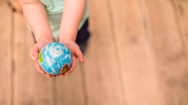 Een bovenaanzicht van handen met globe bal tegen hardhouten vloer Gratis Foto