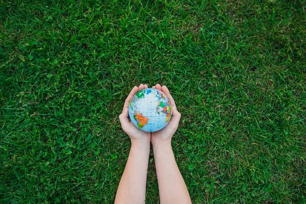 Een bovenaanzicht van handen met globe over groen gras Gratis Foto