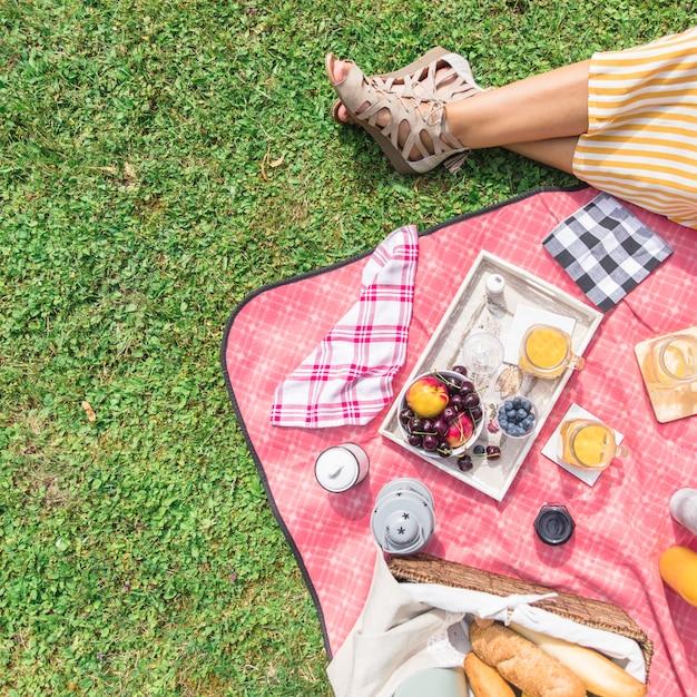 Een bovenaanzicht van het been van de vrouw met ontbijt op picknick over het groene gras Gratis Foto