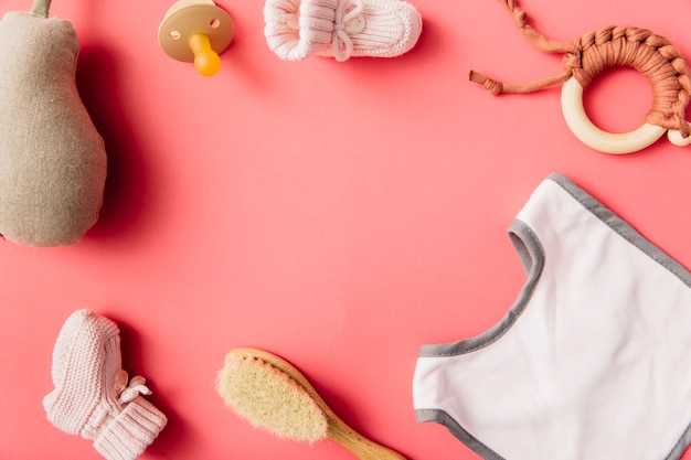 Een bovenaanzicht van het slabbetje van de baby; fopspeen; sok; borstel; gevulde peer en speelgoed op perzik achtergrond Gratis Foto