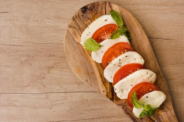 Een bovenaanzicht van italiaanse caprese salade met plakjes mozzarella kaas; basilicum en tomaten op het dienen van raad Gratis Foto