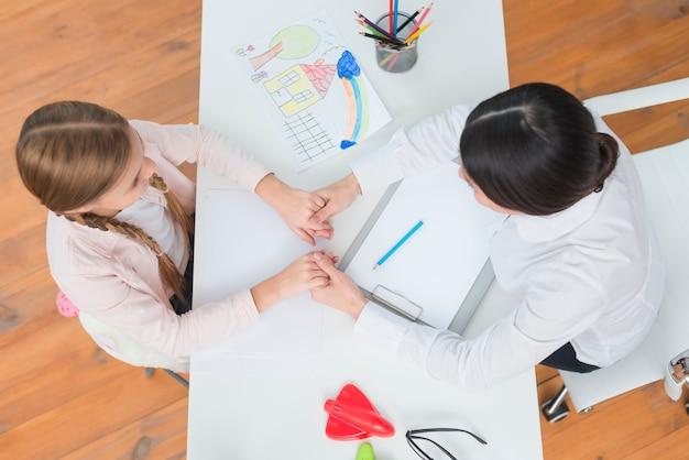 Een bovenaanzicht van klein meisje en vrouwelijke psycholoog houden elkaars hand op witte tafel Gratis Foto