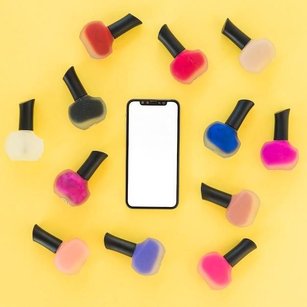 Een bovenaanzicht van leeg scherm smartphone met kleurrijke nail varnish op gele achtergrond Gratis Foto
