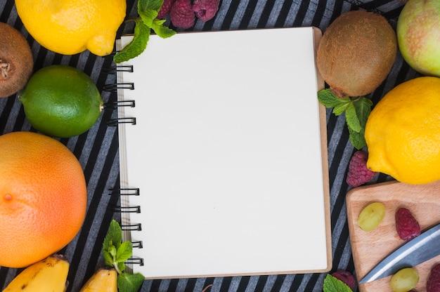 Een bovenaanzicht van lege witte spiraal blocnote met verschillende vers fruit Gratis Foto