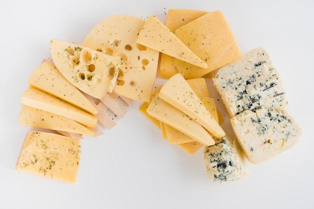 Een bovenaanzicht van maasdam; cheddar; gouda en blauwe kaas op witte achtergrond Gratis Foto