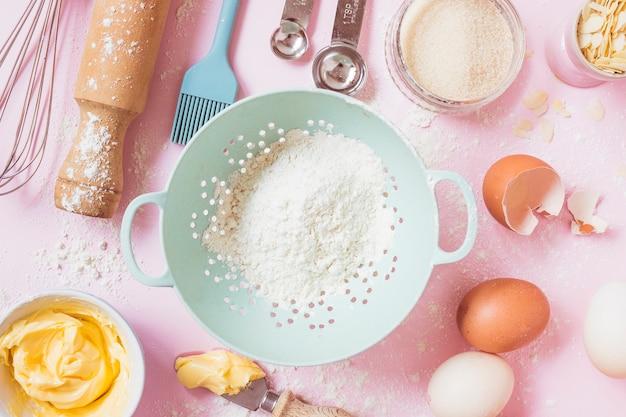 Een bovenaanzicht van meel; eieren; boter en apparatuur op roze achtergrond Gratis Foto