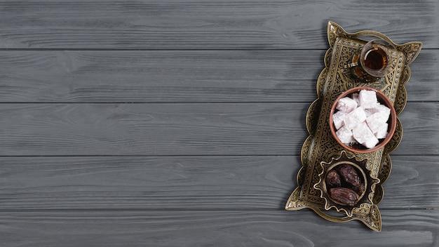 Een bovenaanzicht van metalen dienblad met lukum van turkse verrukking; dadels en thee op ramadan over de houten tafel Gratis Foto
