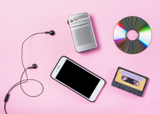 Een bovenaanzicht van mobiel met oortelefoon; cd; radio en cassette op roze achtergrond Gratis Foto
