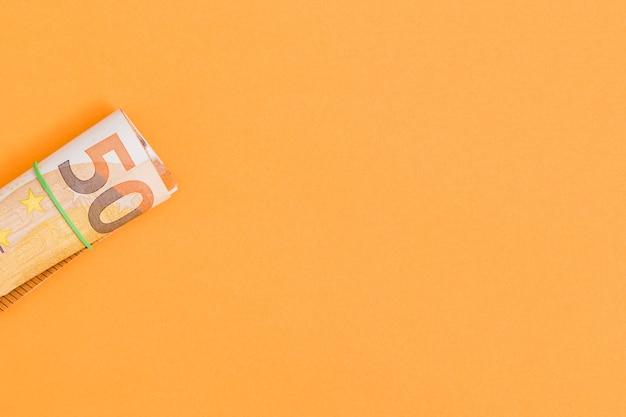 Een bovenaanzicht van opgerolde euro notitie gebonden met rubber op een oranje achtergrond Gratis Foto
