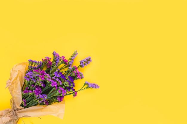 Een bovenaanzicht van paarse bloemboeket op gele achtergrond Gratis Foto