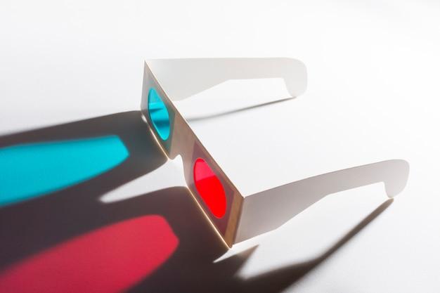 Een bovenaanzicht van rode en blauwe 3d bril op reflecterende achtergrond Gratis Foto