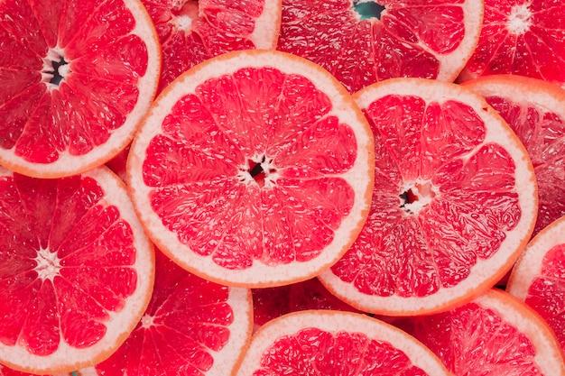 Een bovenaanzicht van sappige rode grapefruits plakjes achtergrond Gratis Foto
