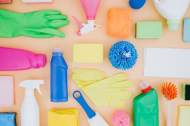 Een bovenaanzicht van schoonmaakproducten stilleven op perzik achtergrond Gratis Foto
