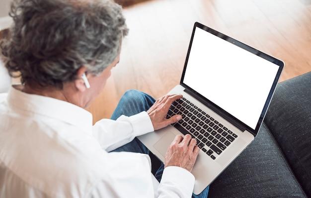 Een bovenaanzicht van senior man draagt â € <â € <bluetooth oortelefoon met behulp van laptop Gratis Foto