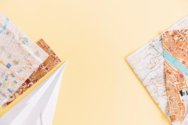 Een bovenaanzicht van steden wegenkaarten en papieren vliegtuigje op gekleurde achtergrond Gratis Foto