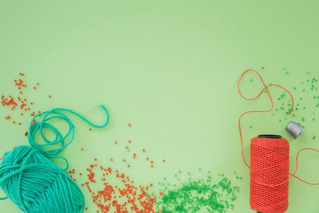 Een bovenaanzicht van tang; schaar; kralen en spoel op groene achtergrond Gratis Foto