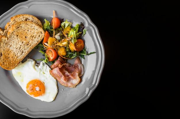 Een bovenaanzicht van toast; spek; salade en gebakken eieren op grijze plaat op zwarte achtergrond Gratis Foto