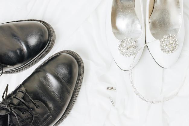 Een bovenaanzicht van trouwringen; kroon en schoenen op witte doek Gratis Foto