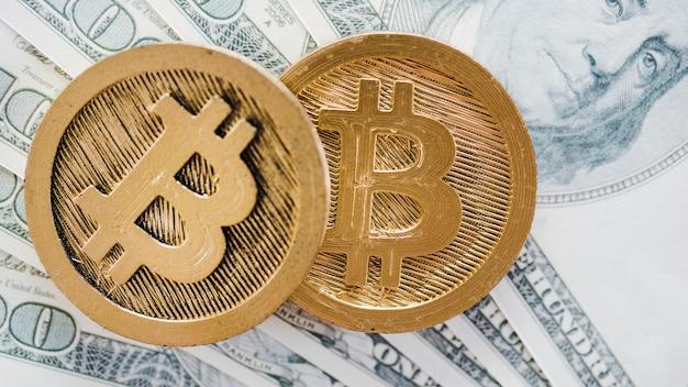 Een bovenaanzicht van twee bitcoins verspreidde zich over de dollarbiljetten Gratis Foto