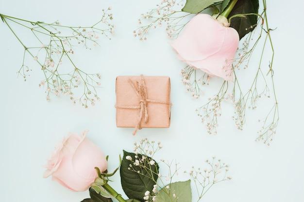 Een bovenaanzicht van verpakt geschenkdoos met bloemen op blauwe gekleurde achtergrond Gratis Foto