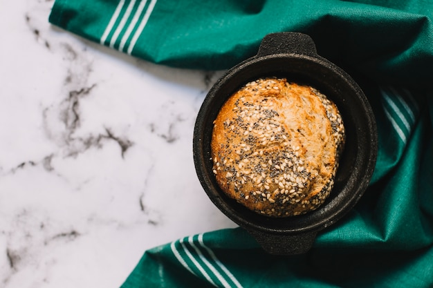 Een bovenaanzicht van vers gebakken brood in gebruiksvoorwerp met groene servet over marmeren achtergrond Gratis Foto