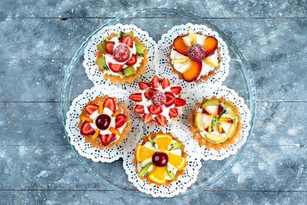 Een bovenaanzicht van verschillende kleine cakes met room en vers gesneden fruit op het grijsblauwe koekje van de fruitcake Gratis Foto