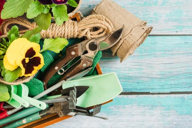 Een bovenaanzicht van viooltjesplanten; turf potten en tuinieren apparatuur op het bureau Gratis Foto