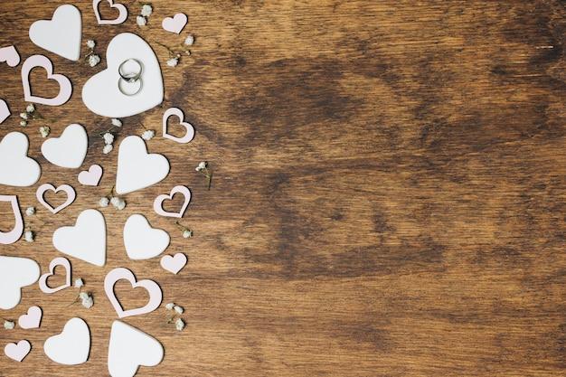 Een bovenaanzicht van zilveren trouwringen op hartvorm over de houten achtergrond Gratis Foto