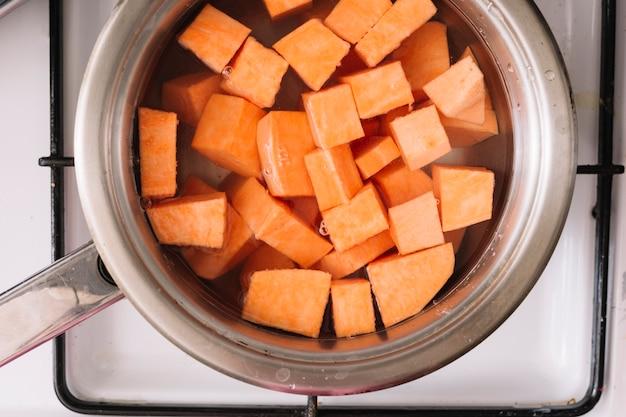 Een bovenaanzicht van zoete aardappelen plak koken in de metalen pan op gas Gratis Foto