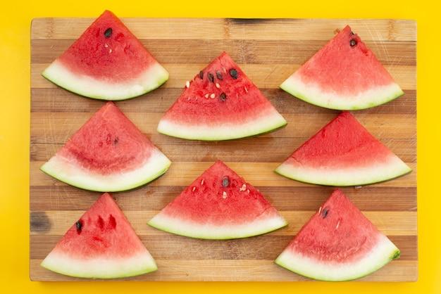 Een bovenaanzicht vers gesneden watermeloen zacht en zoet op bruin houten en geel, fruit zomerkleur Gratis Foto